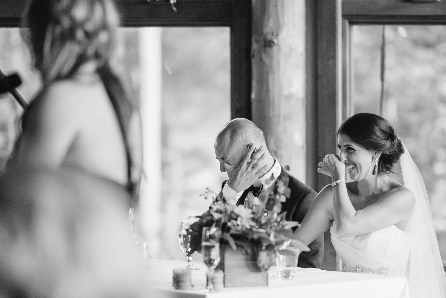Red Pine Lodge bride and groom laughing during speeches wedding photo