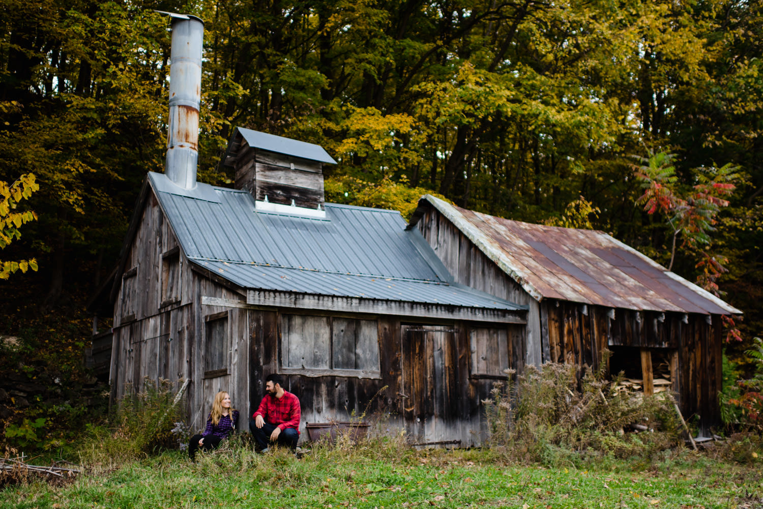 Burlington, Vermont Autumn Engagement couple sitting with each other by a cabin photo