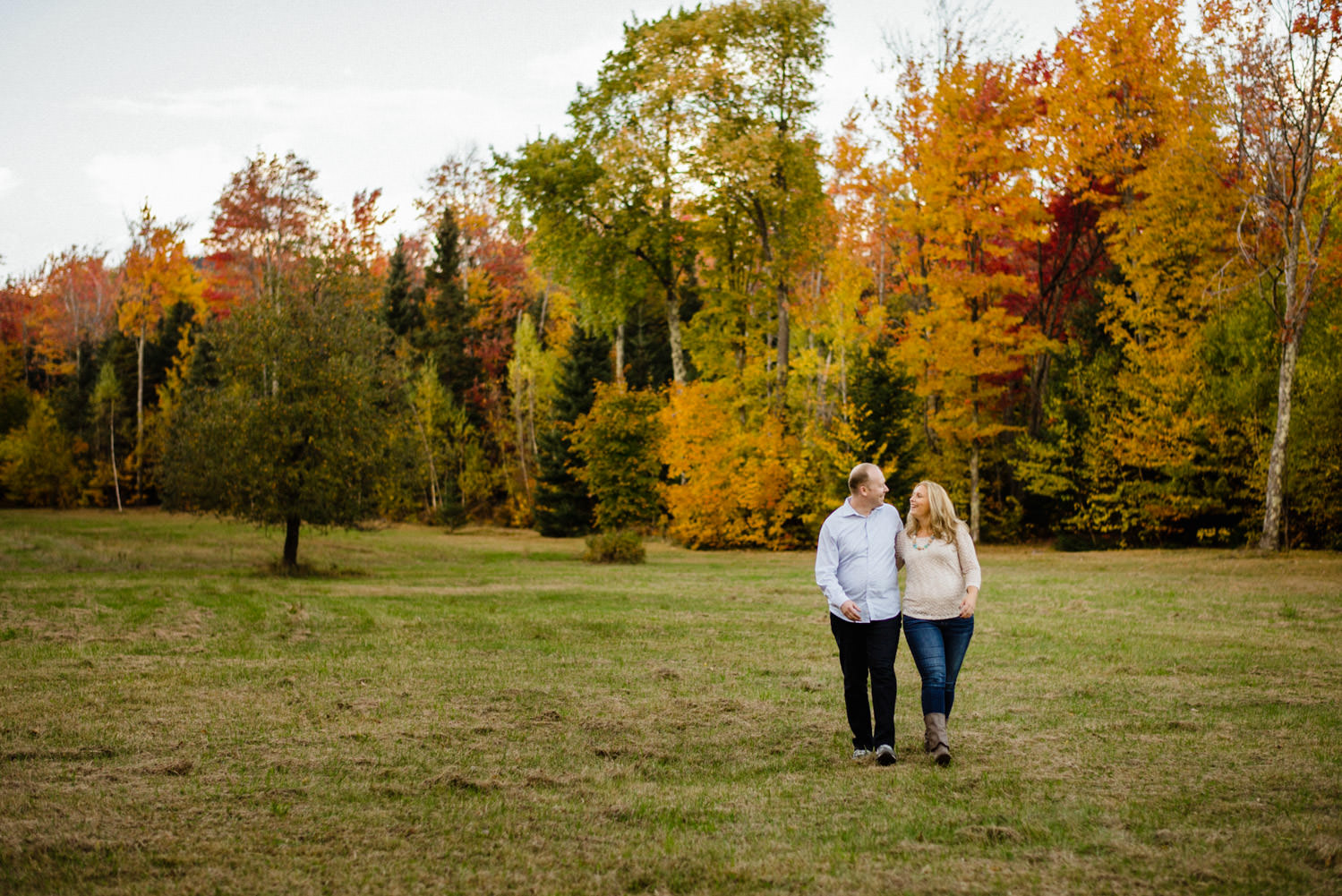 Vermont Fall Colors Engagement couple walking arm-in-arm photo