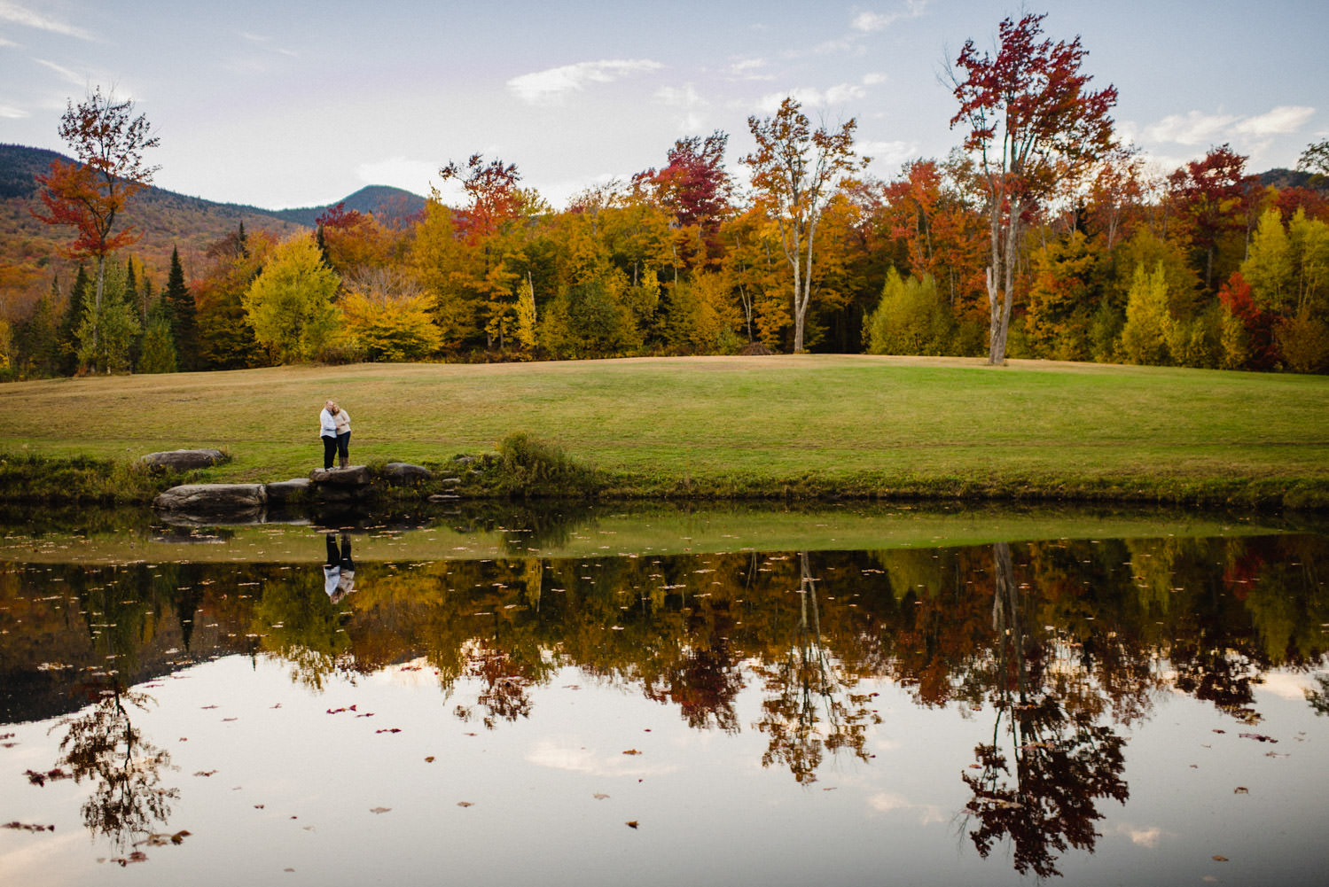 Vermont Fall Colors Engagement couple embracing by the water photo