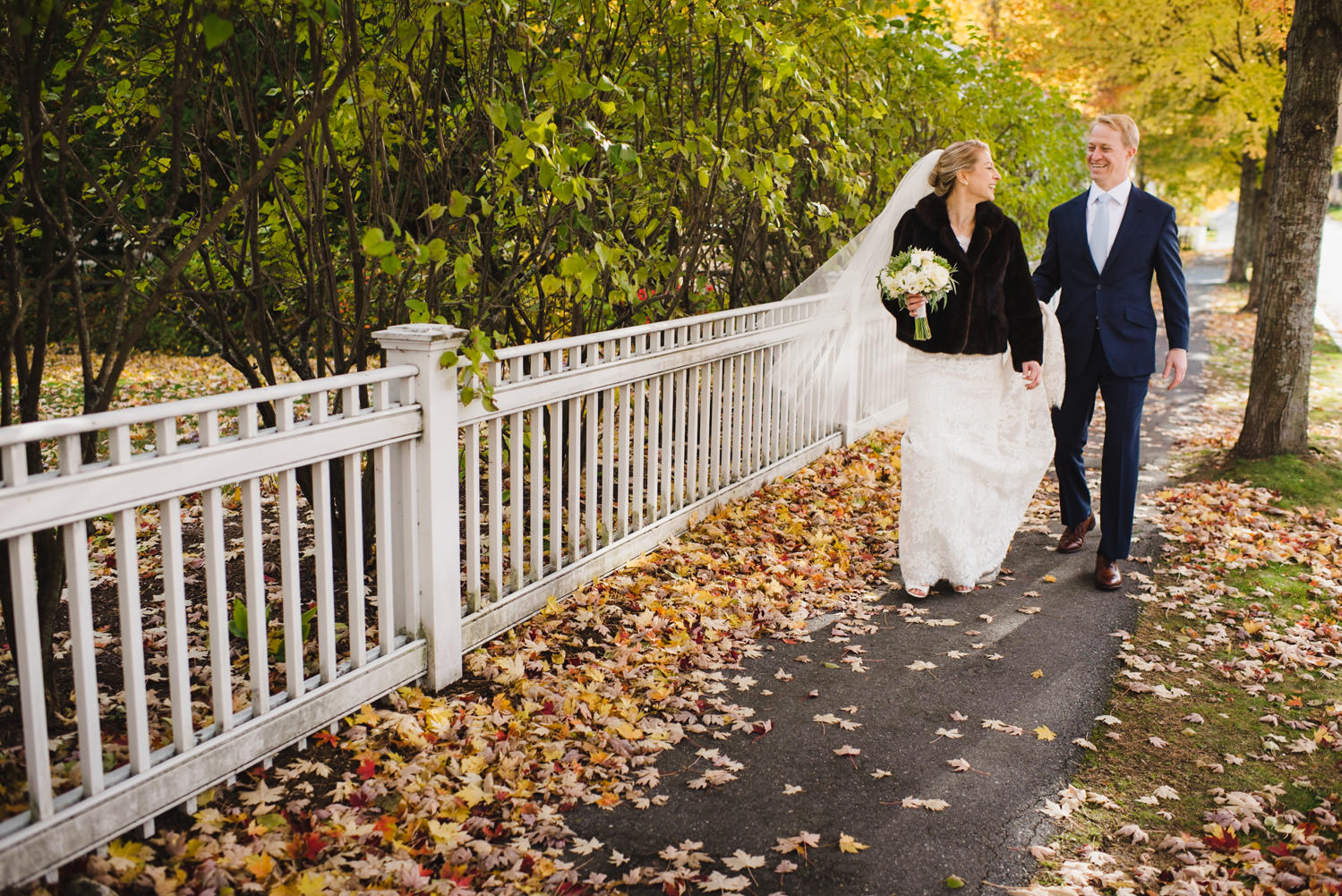 Woodstock, Vermont Wedding newlyweds walking in fall leaves photo