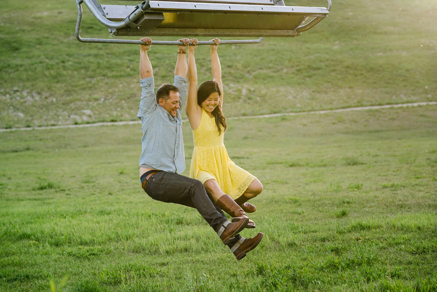 Solitude Mountain Resort Engagement couple laughing and hanging from a chairlift photo