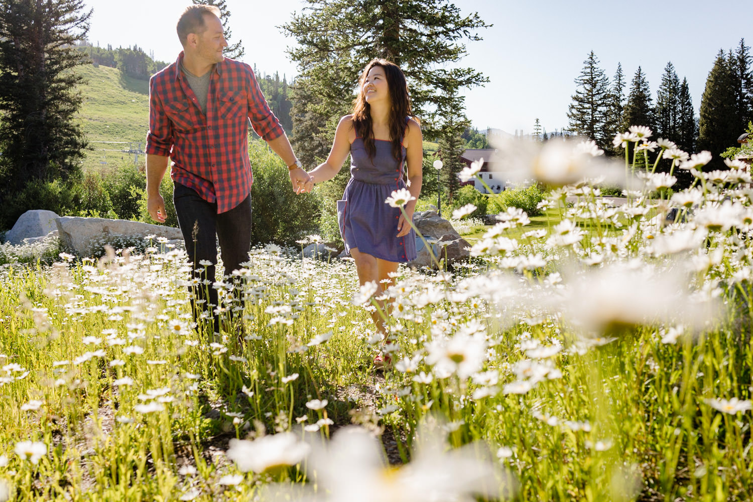 Solitude Mountain Resort Engagement couple holding hands in meadow smiling photo