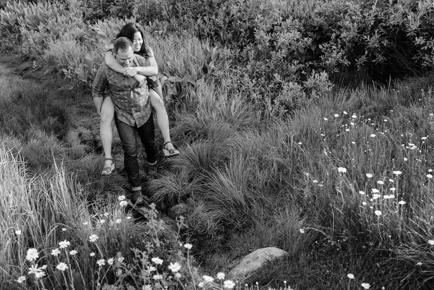 Solitude Mountain Resort Engagement man carrying his fiancée through a meadow photo