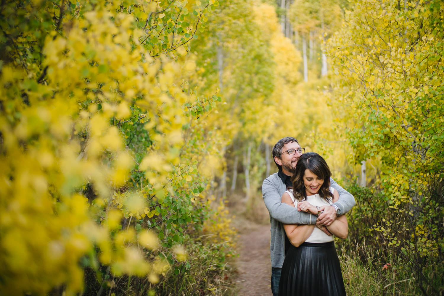 Millcreek Engagement man hugging his bride-to-be from behind photo