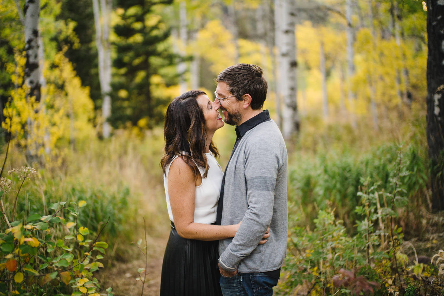 Millcreek Engagement woman smiling as she kisses her future husband photo