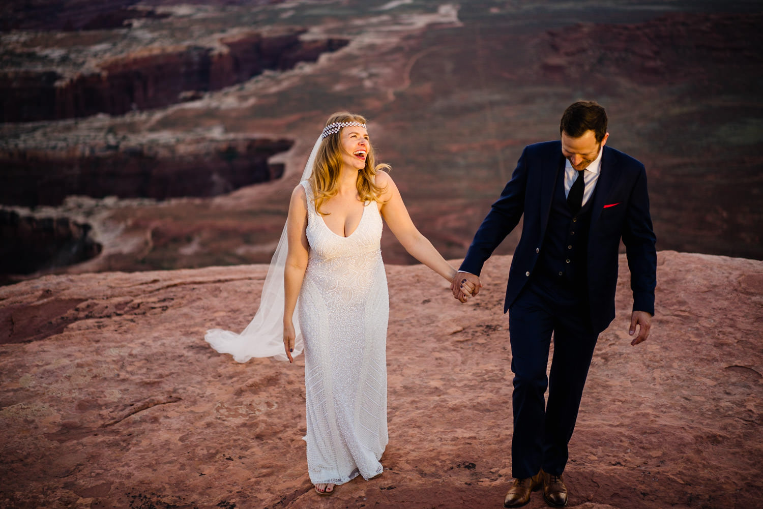 Canyonlands National Park Wedding bride and groom laughing and holding hands photo