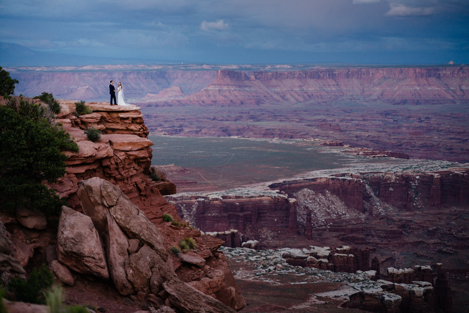 Canyonlands National Park Wedding bride and groom atop at cliff photo