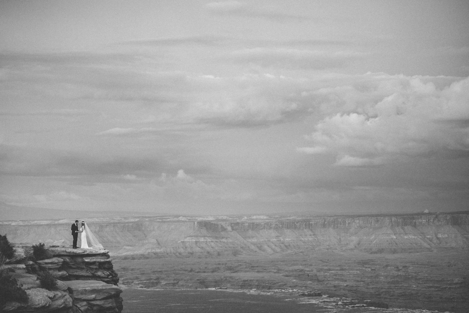 Canyonlands National Park Wedding bride and groom atop a cliff black and white photo