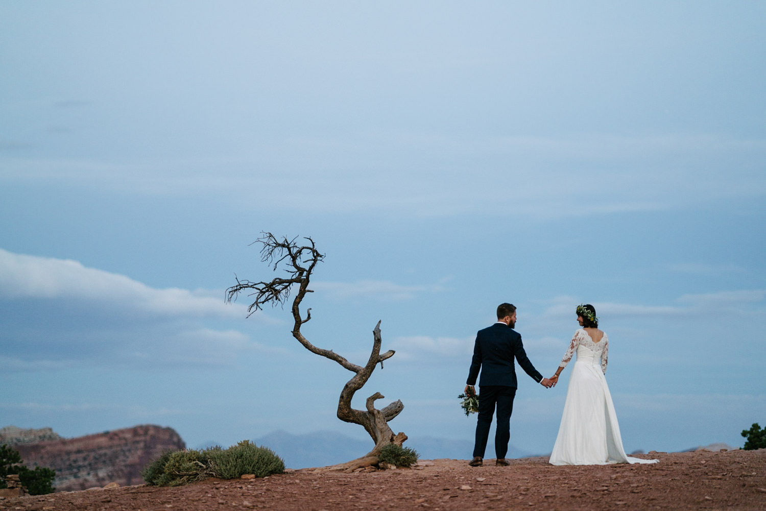 Capitol Reef National Park Wedding bride and groom holding hands at dusk photo