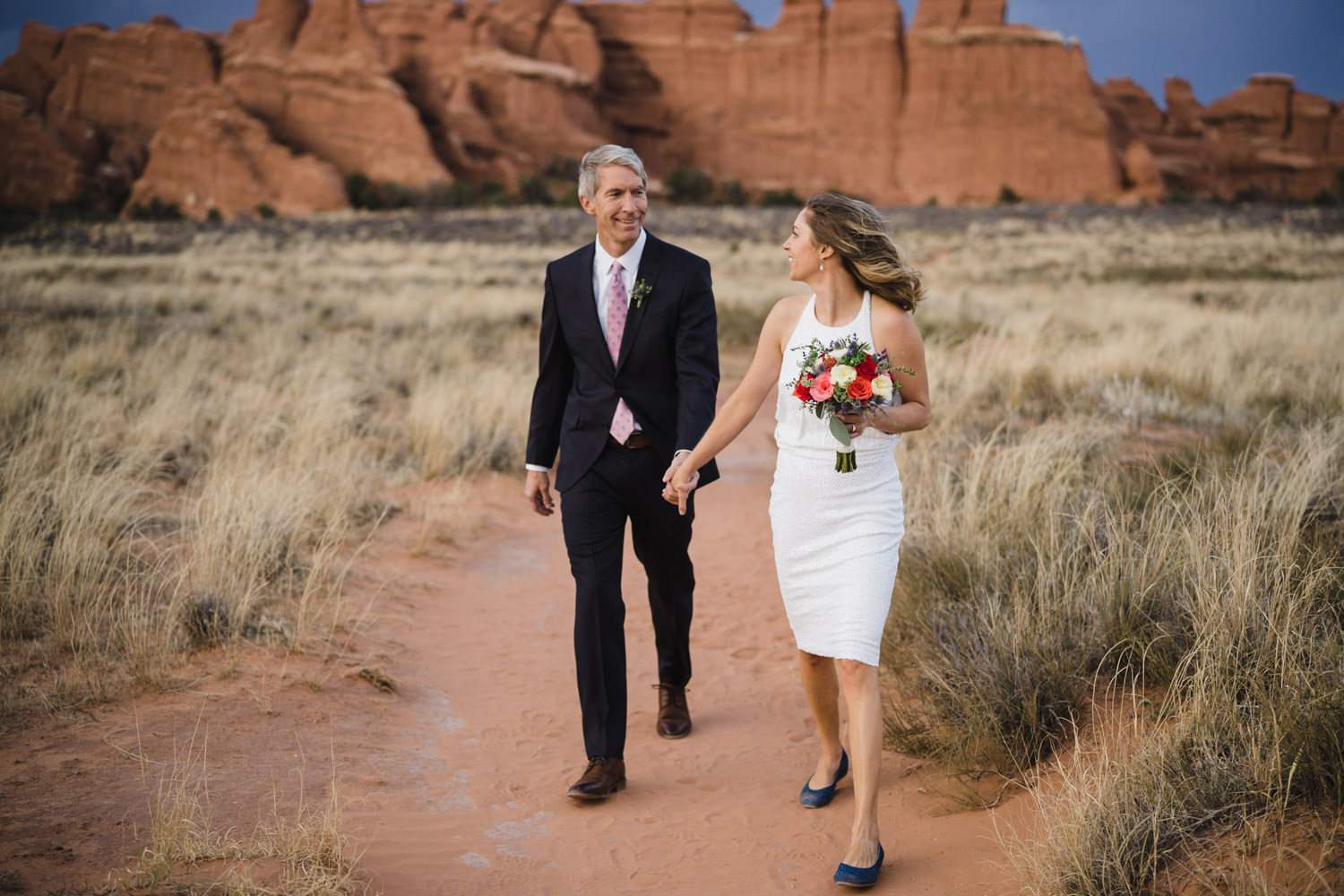 Arches engagement couple holding hands on path photo