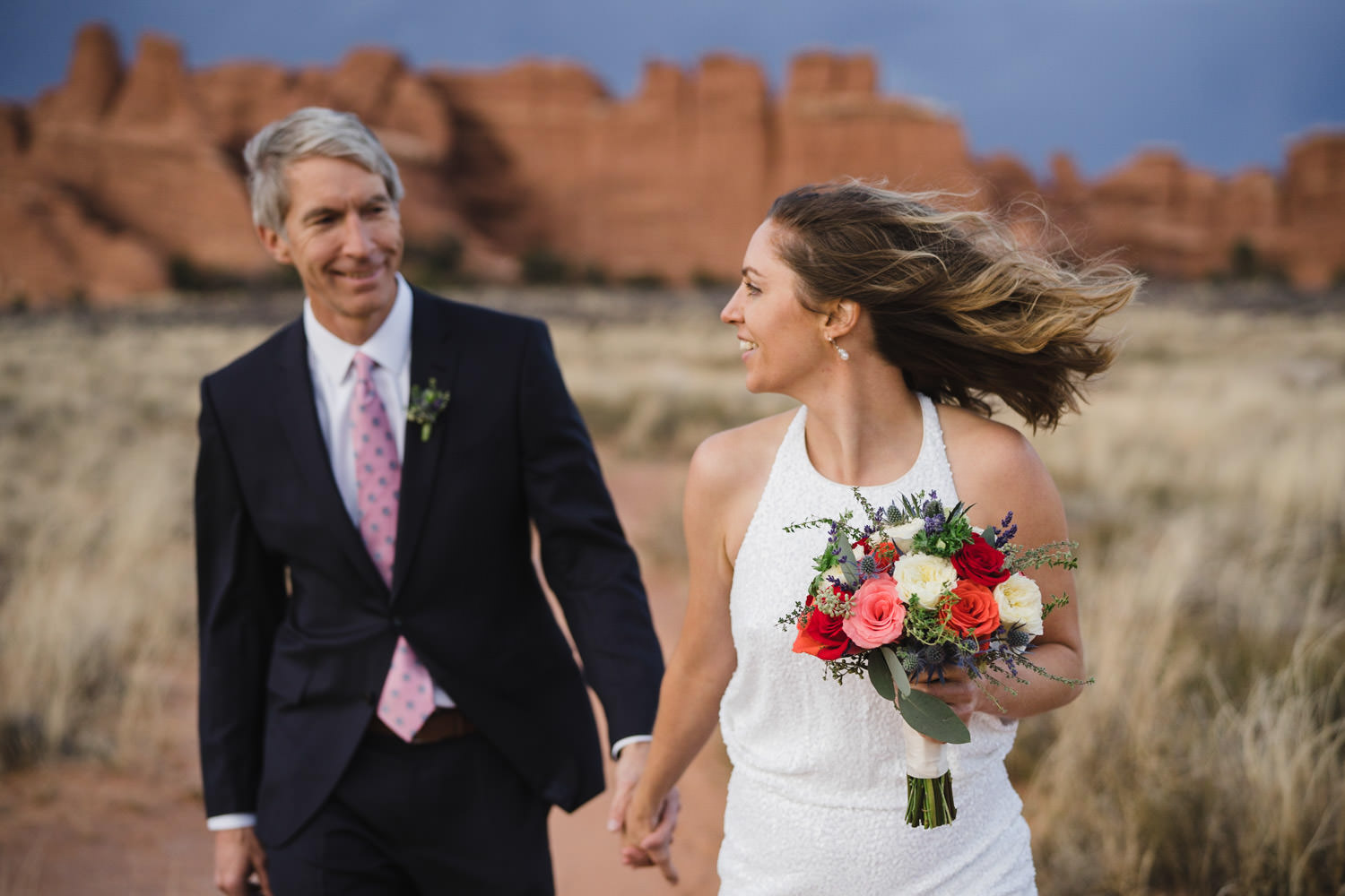 Arches engagement couple sharing smiles while walking photo