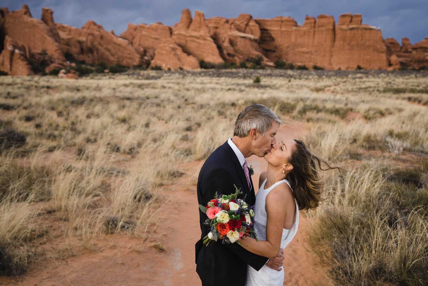Arches engagement couple kissing with rock and grass landscape photo
