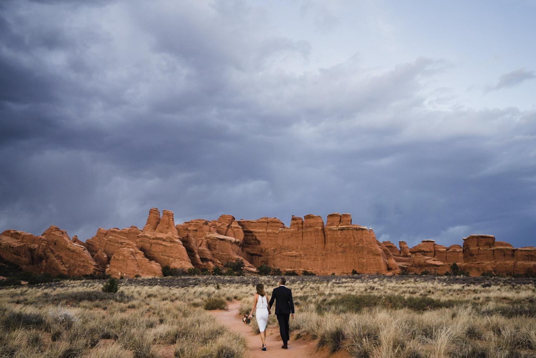 Arches engagement couple walking towards rock structure photo