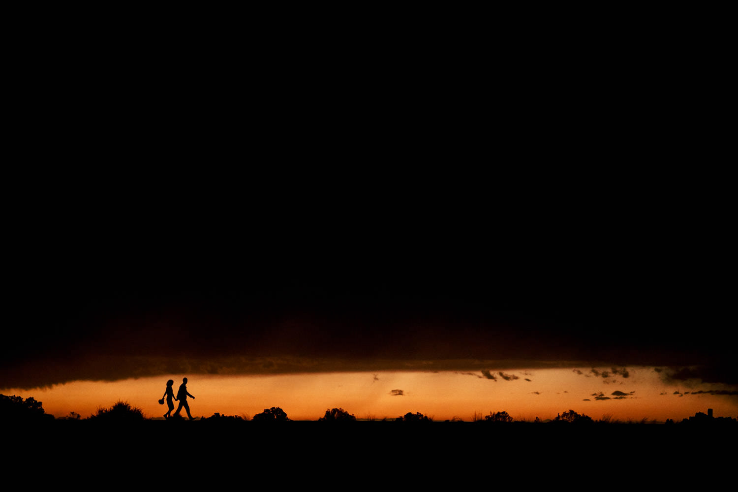 Arches engagement couple silhouette with orange glow sky photo