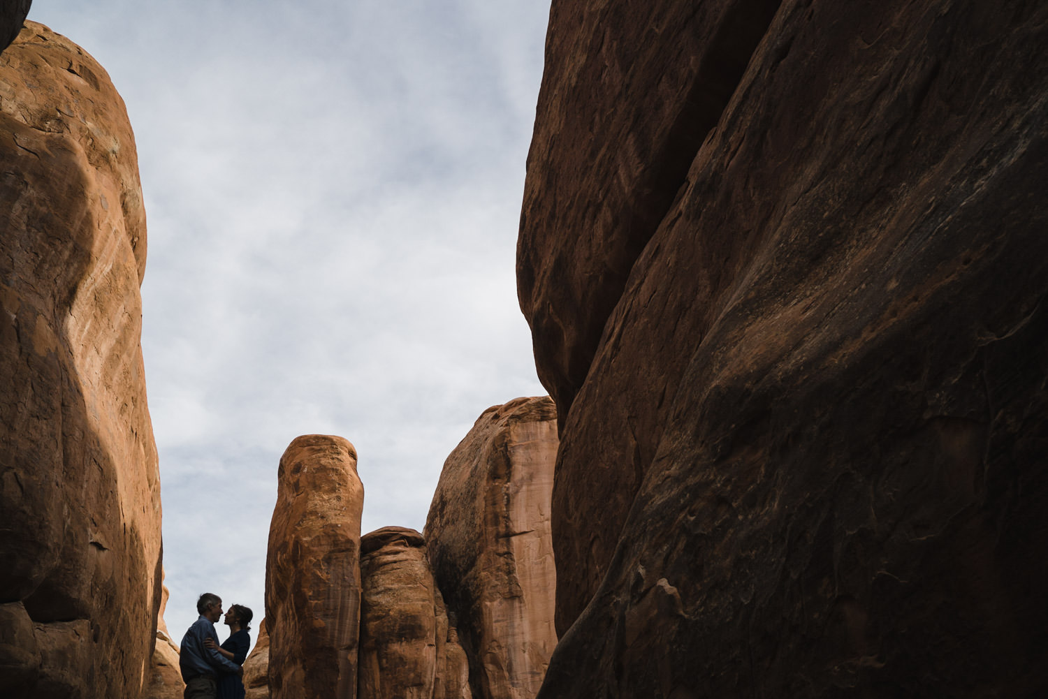 Arches engagement couple hugging in slot canyons photo