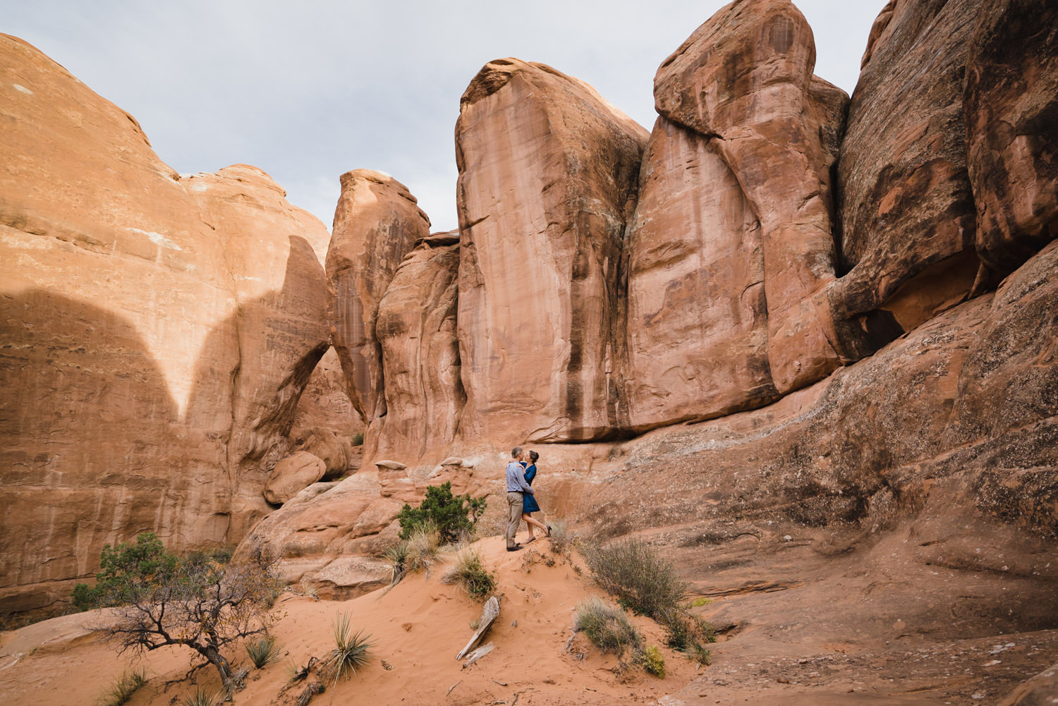 Arches engagement copule hugging in front of rock fins photo