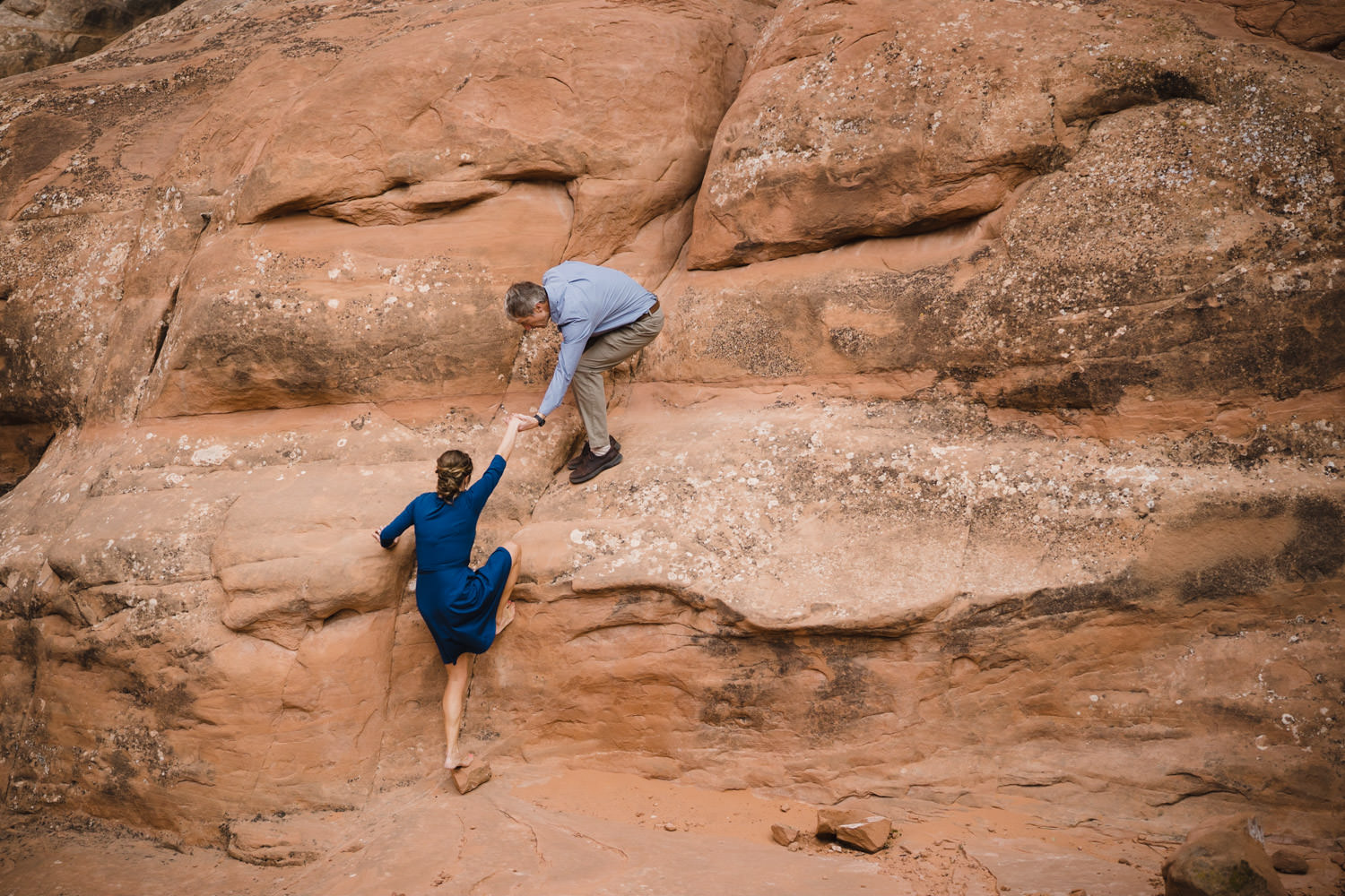 Arches engagement man helping woman to climb up rocks photo
