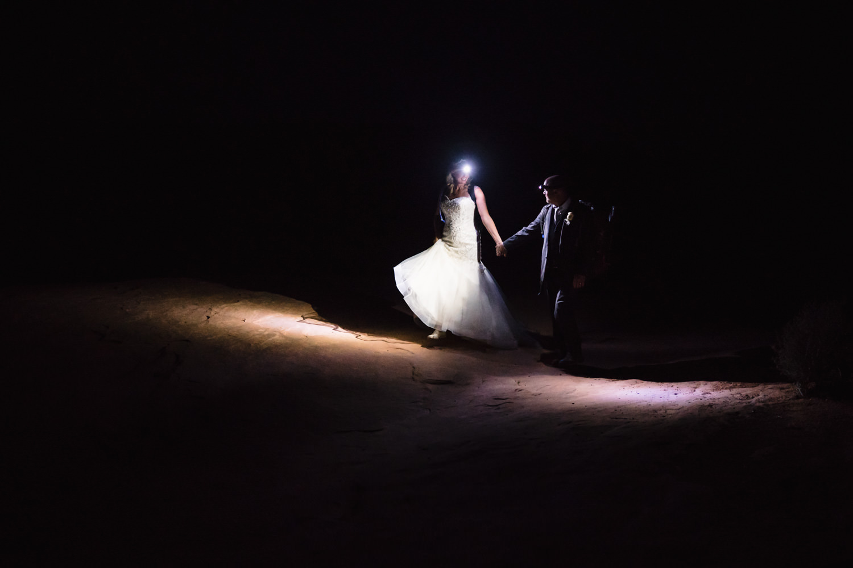 Night sky wedding bride and groom walking in dark with headlamp photo