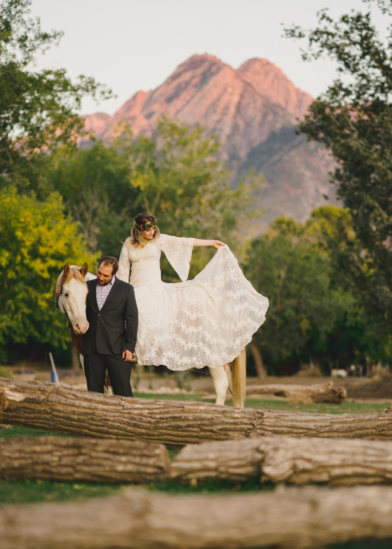 Equestrian bridal session bride admiring gown while on horse photo