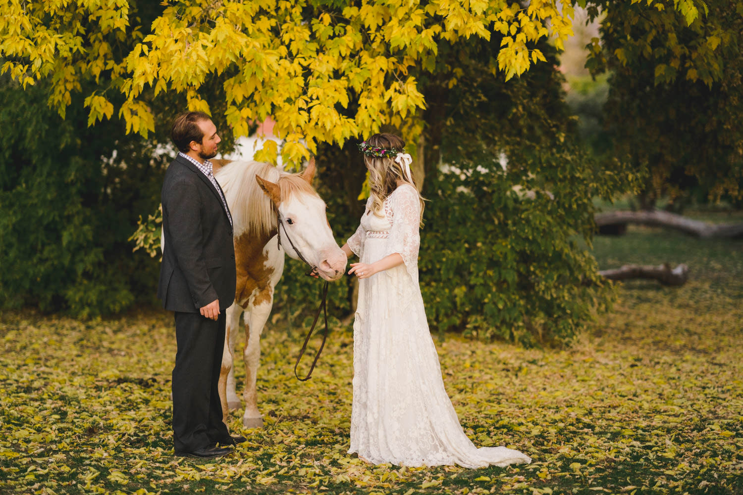 Equestrian bridal session couple with horse in fall leaves photo
