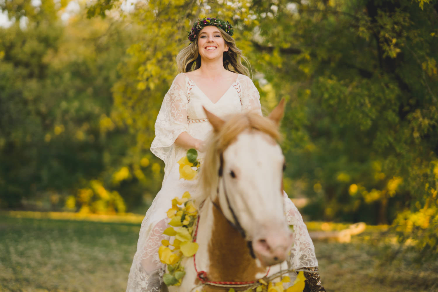 Equestrian bridal session bride smiling on horse with yellow flowers photo