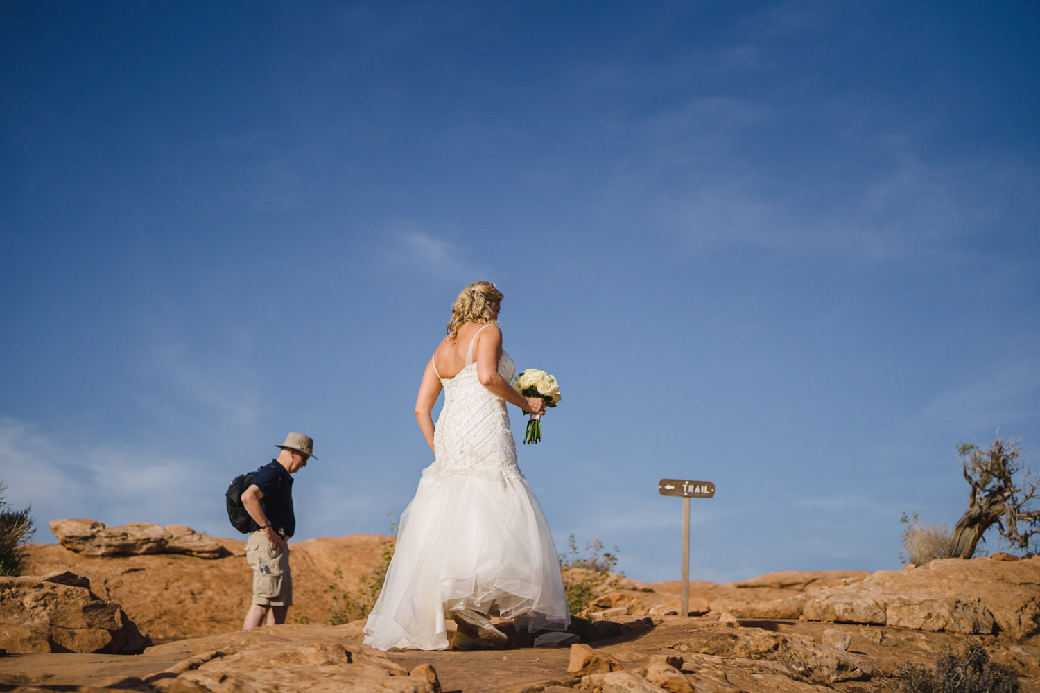 Delicate Arch elopement bride approaching trail sign photo