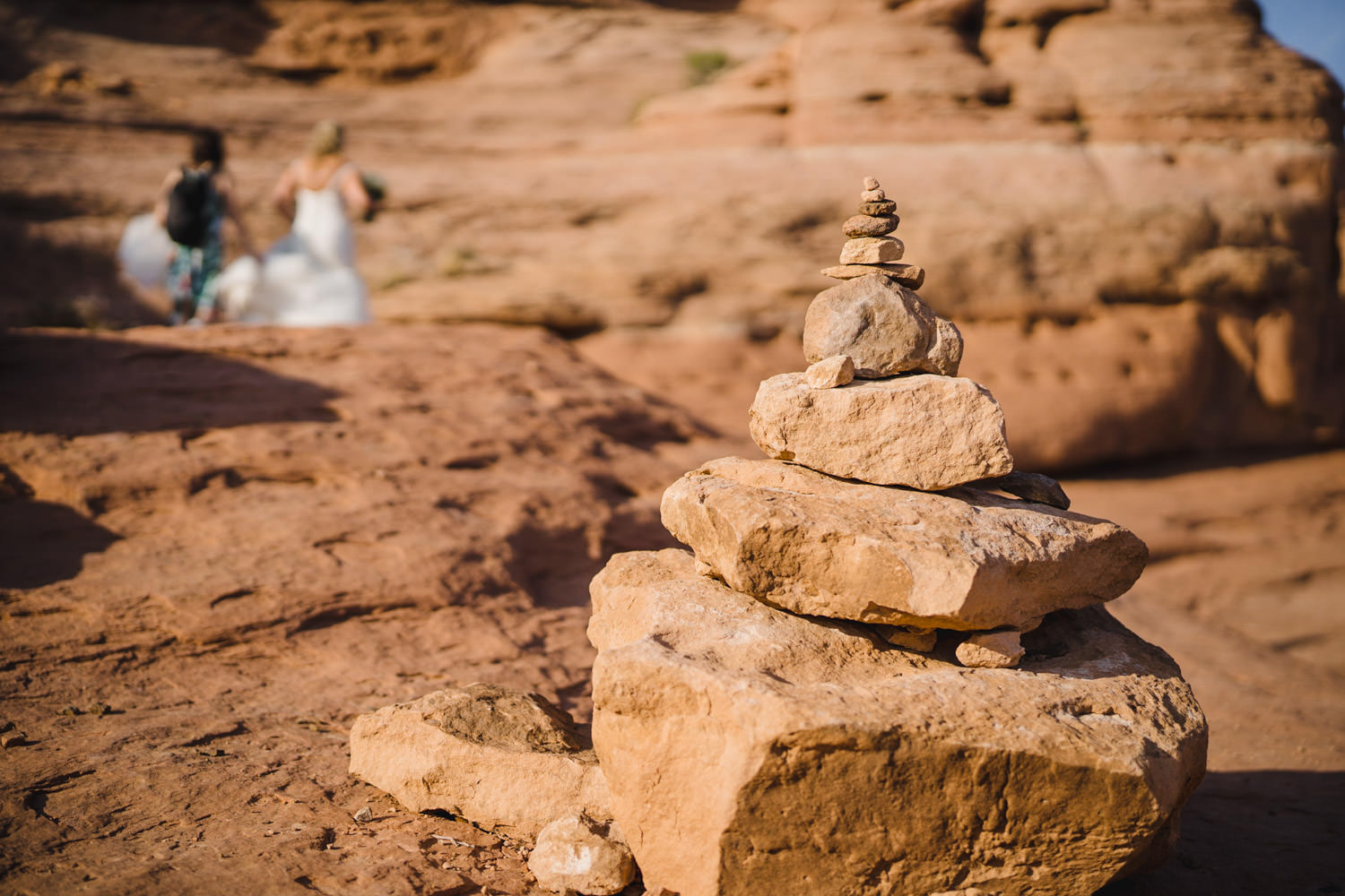 Delicate Arch elopement cairn with bride in background photo