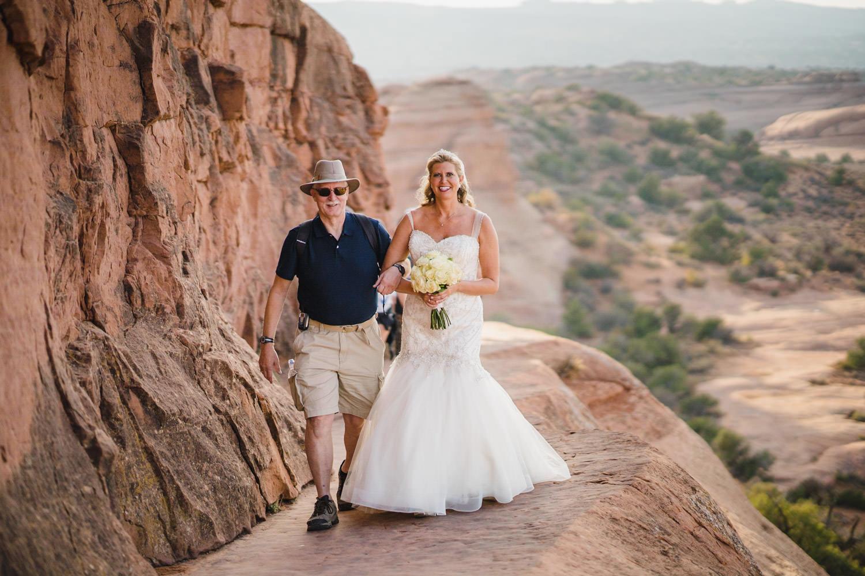 Delicate Arch elopement bride walking along edge photo