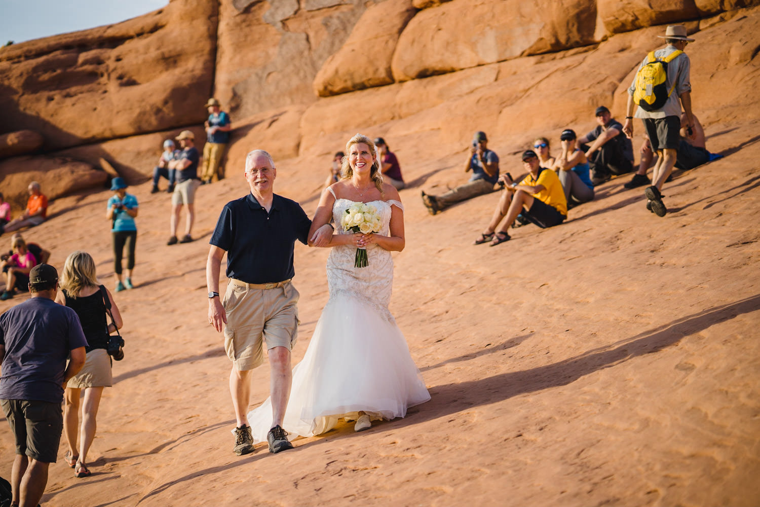Delicate Arch elopement bride walking to ceremony with onlookers photo