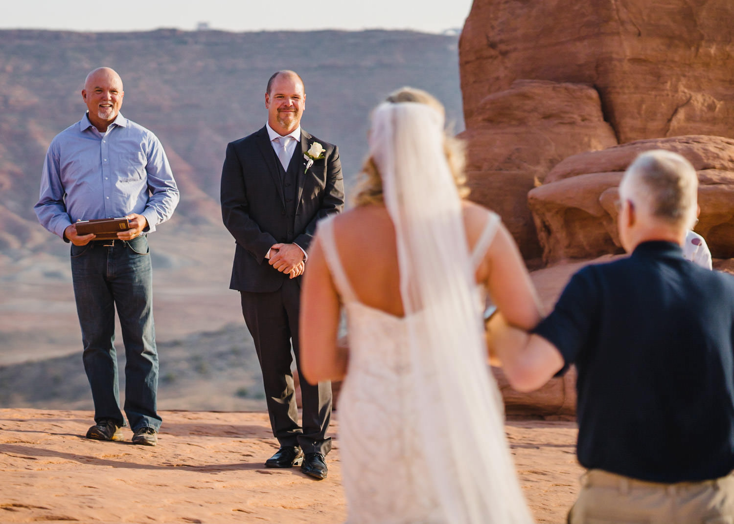 Delicate Arch elopement bride walking to groom for ceremony photo