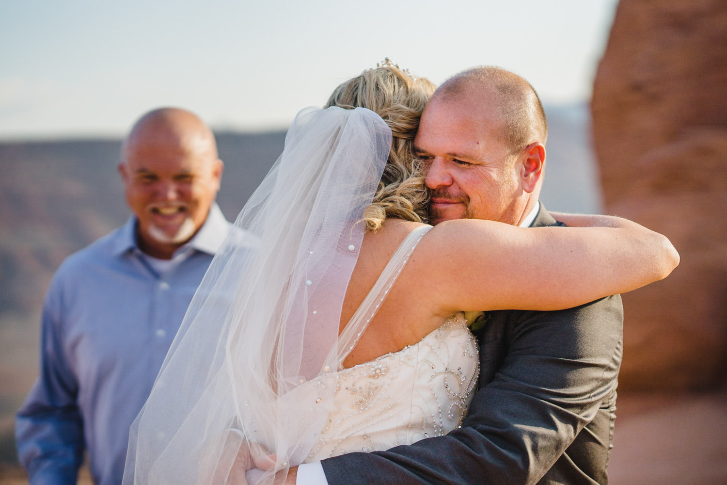 Delicate Arch elopement bride and groom hugging photo