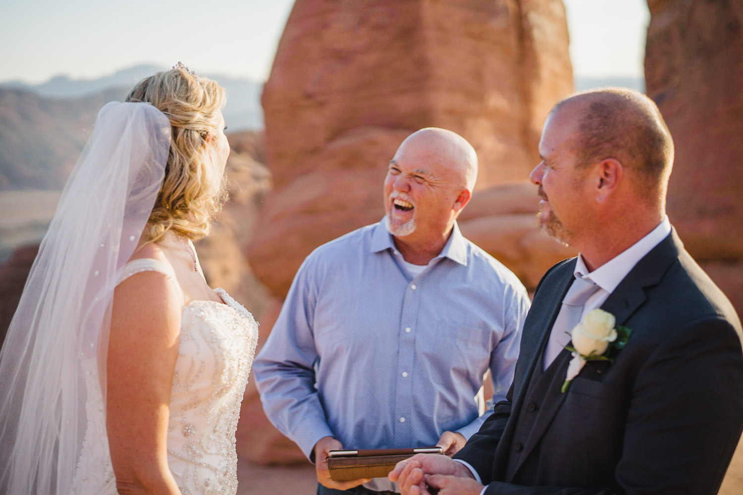 Delicate Arch elopement bride and groom laughing with officiant photo
