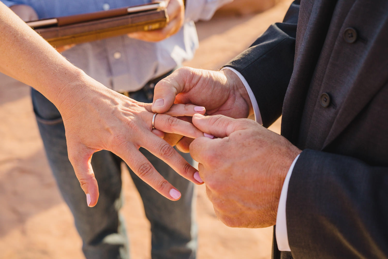 Delicate Arch elopement exchanging rings photo