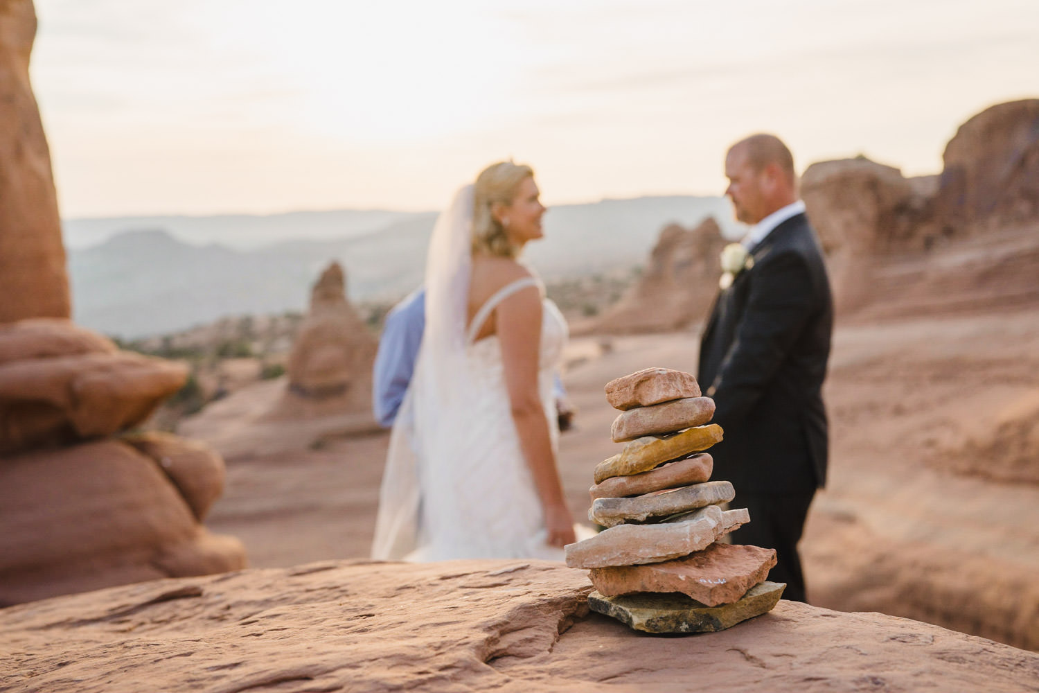 Delicate Arch elopement bride and groom with stacked rocks photo