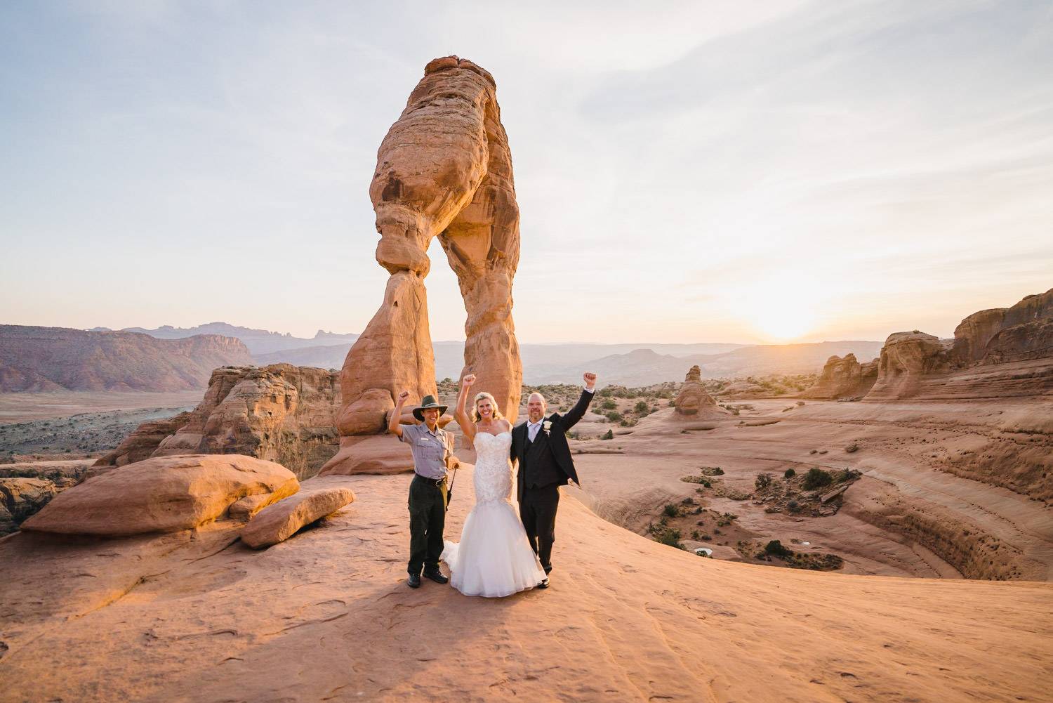 Delicate Arch elopement bride and groom with park ranger photo