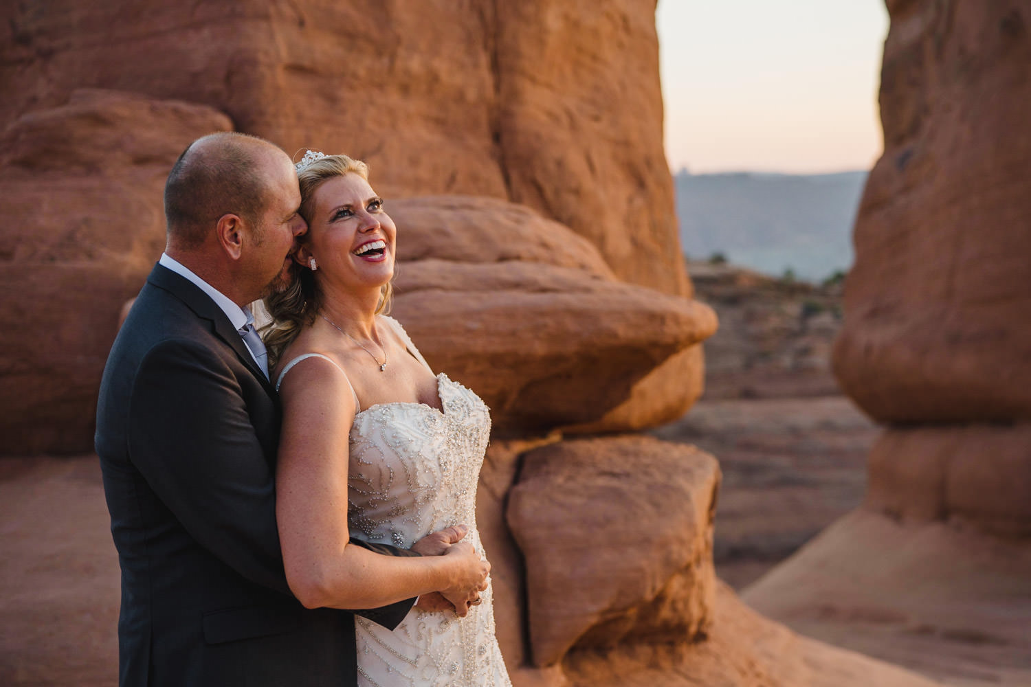 Delicate Arch elopement bride and groom hugging and laughing photo