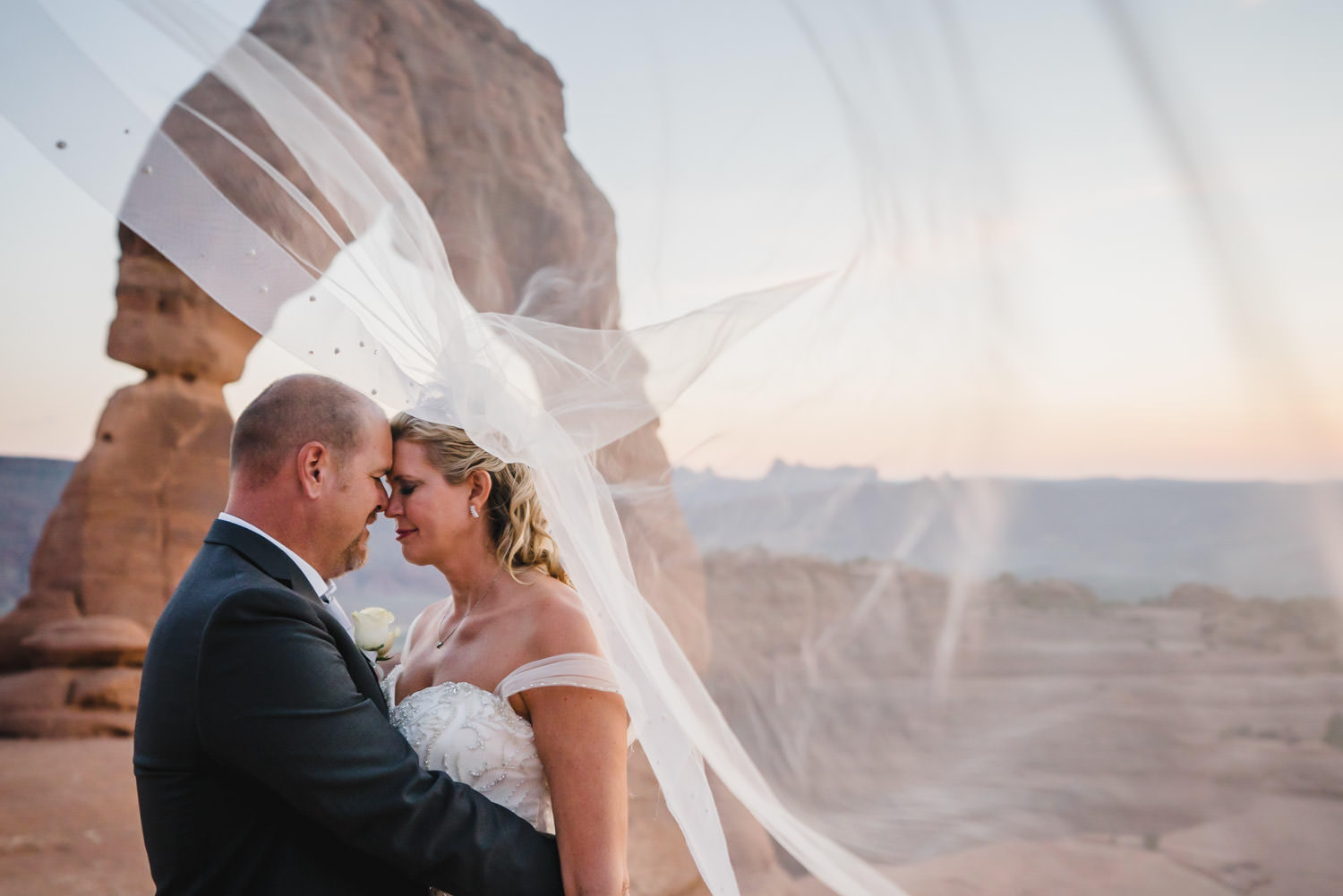 Delicate Arch elopement intimate moment with veil in the wind photo