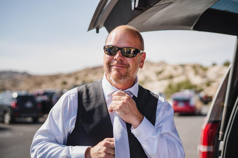 Delicate Arch elopement groom straightening his tie photo
