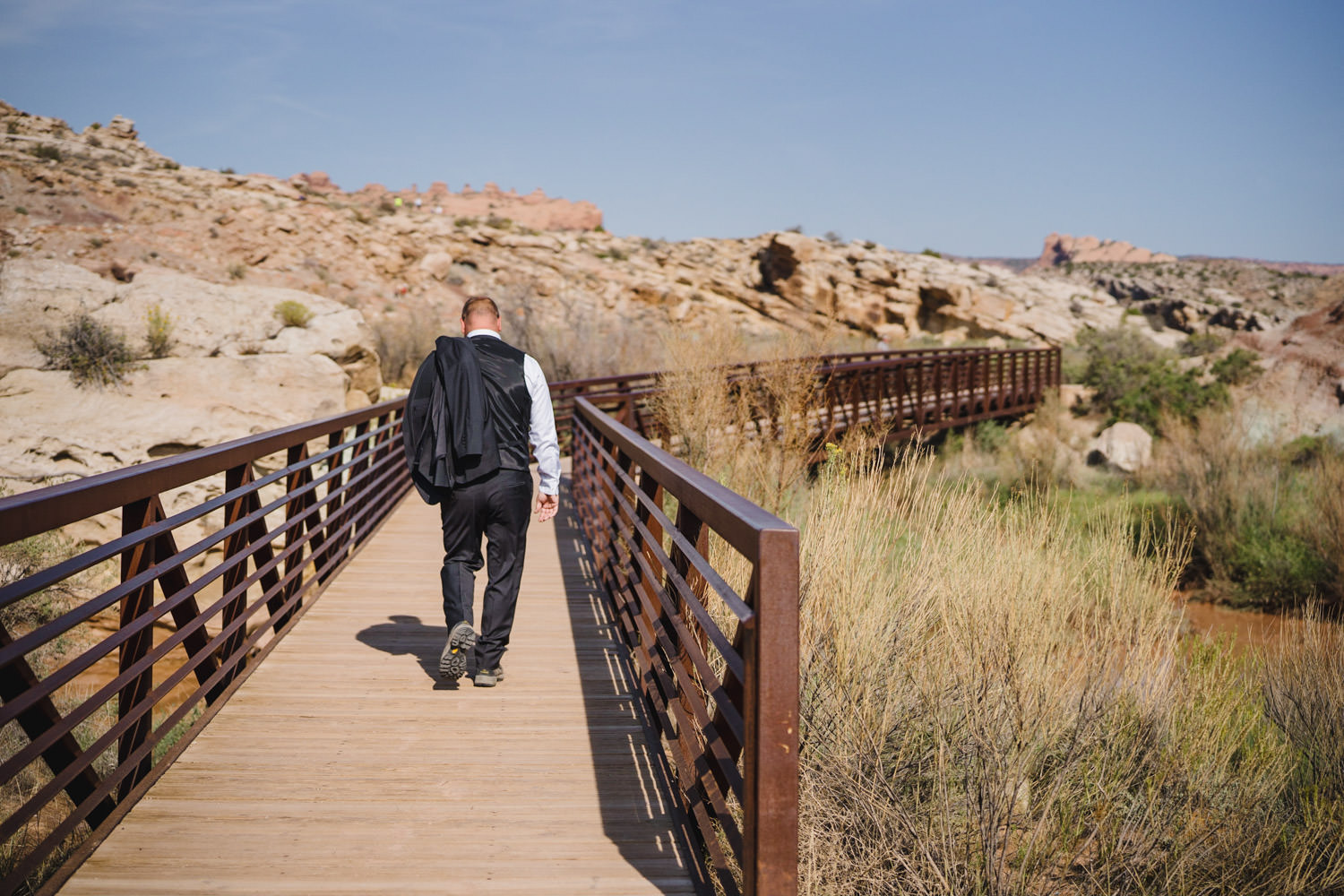 Delicate Arch elopement groom walking on path photo