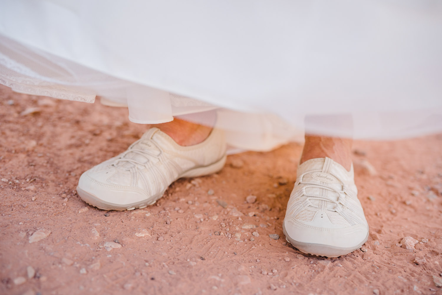 Delicate Arch elopement bride in white sneakers photo