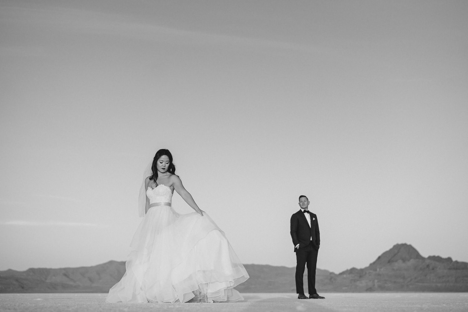 Bonneville Salt Flats wedding bride in gown with groom admiring photo