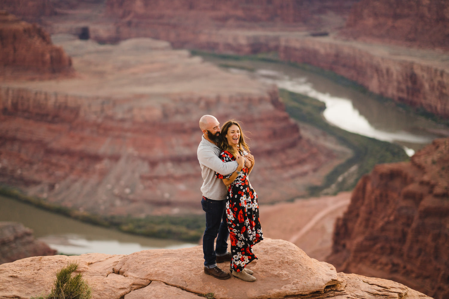 Dead Horse Point engagement couple hugging and laughing on red rocks photo