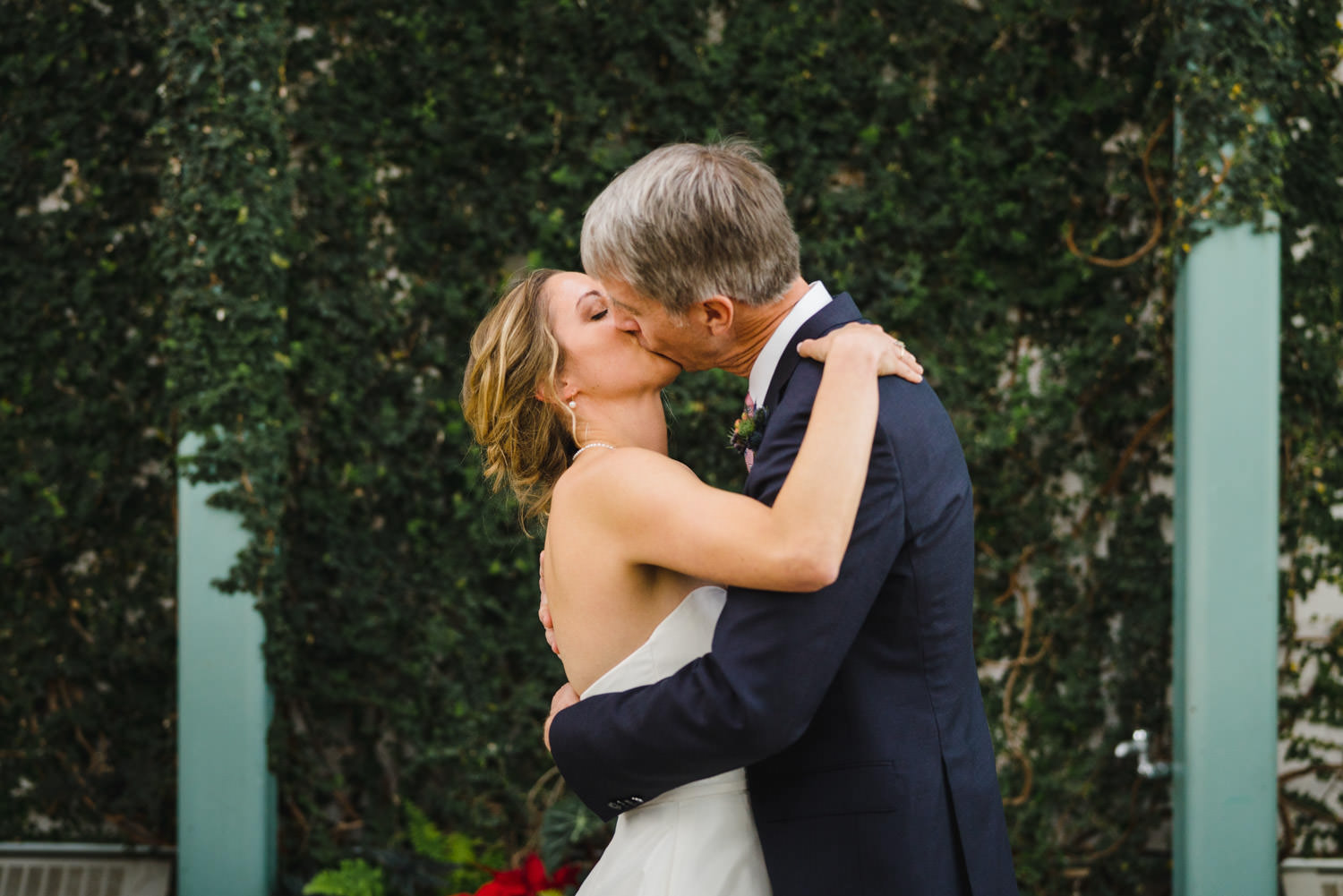 Red Butte Garden wedding bride and groom kiss during ceremony photo