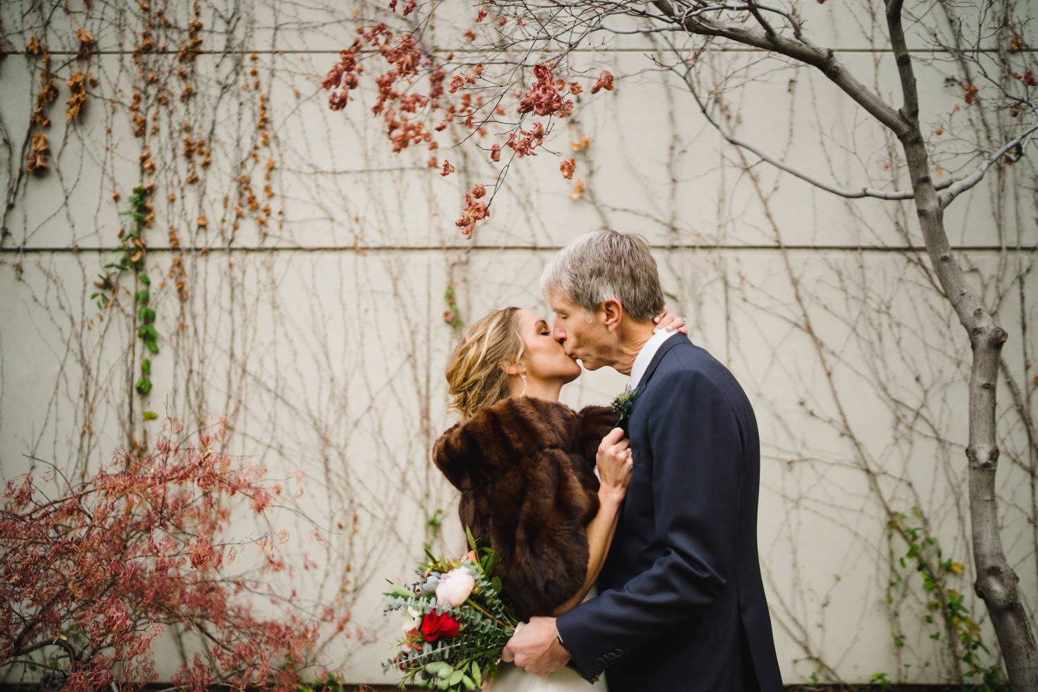 Red Butte Garden wedding bride and groom kissing in front of vines photo