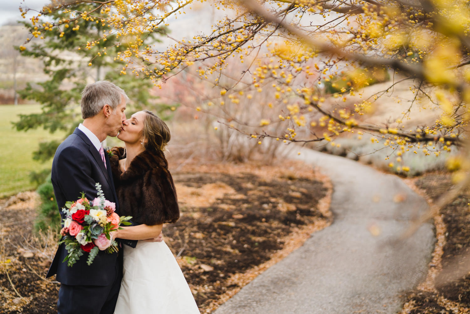Red Butte Garden wedding bride and groom kissing on colorful path photo