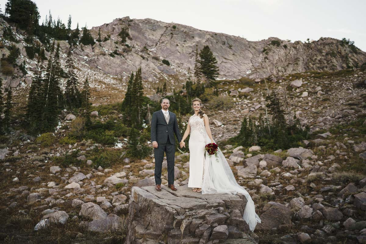 Snowbasin wedding couple holding hands on rock perch photo