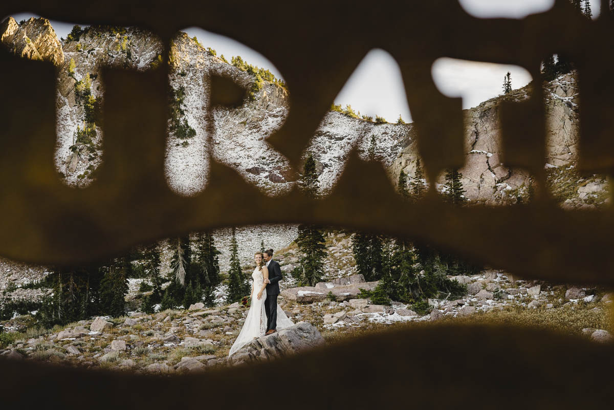 Snowbasin wedding bride and groom through trail sign photo