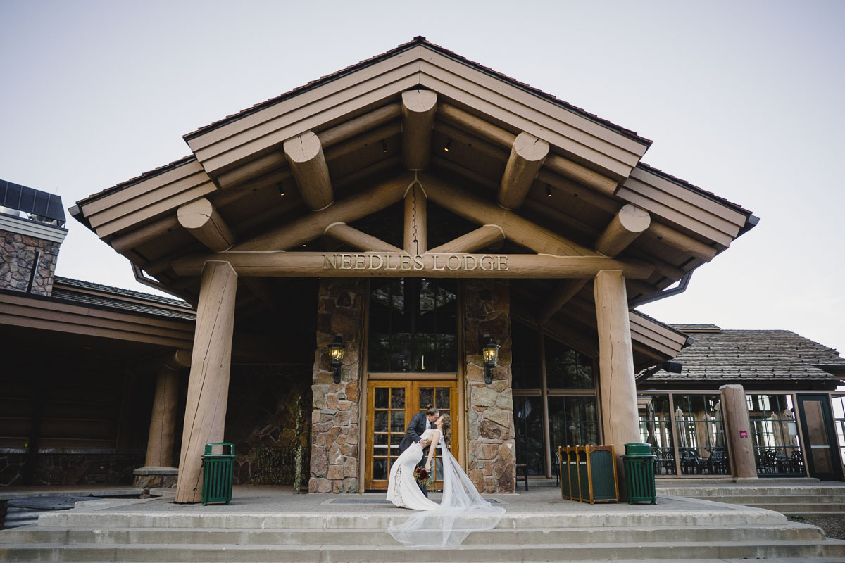 Snowbasin wedding groom dipping bride for kiss in front of Needles Lodge photo