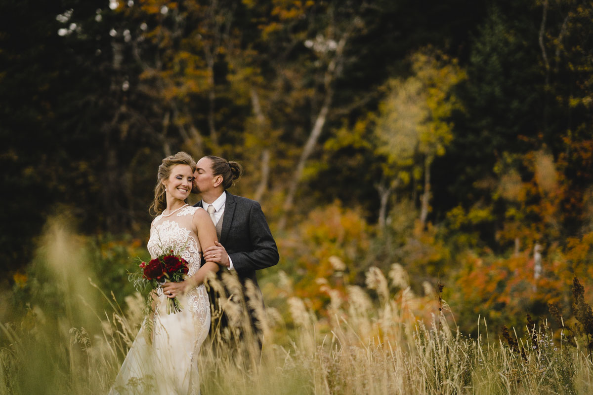 Snowbasin wedding groom kissing bride with colorful fall background photo